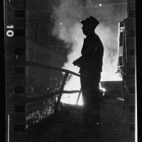 16.-Steel-worker-standing-in-mill-with-smelter-in-the-background-in-Chicago-Illinois