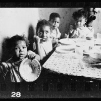 18.-African-American-children-seated-around-a-table-in-an-apartment-eating