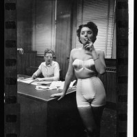 21.-Lingerie-model-wearing-a-girdle-and-strapless-bra-smoking-in-an-office-in-the-background-a-woman-sits-at-a-desk