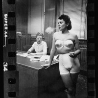 22.-Woman-model-standing-in-an-office-smoking-while-modeling-undergarments