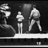 29.-A-wrestler-strides-toward-Gorgeous-George-who-stands-near-a-corner-of-the-ring-with-his-hands-on-his-chest-where-he-had-received-a-blow-in-the-previous-maneuver-in-the-wrestling-match